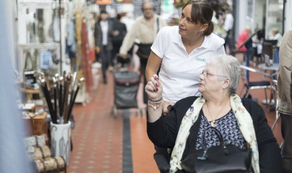 Carer Taking Lady in Wheelchair Shopping