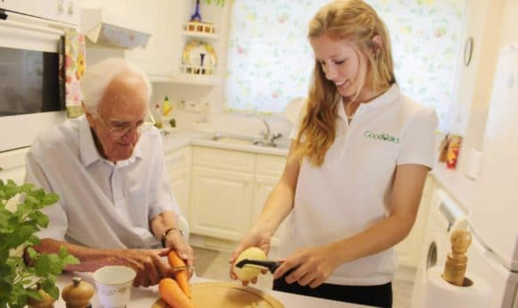 Female carer helping elderly gentleman to prepare vegetables